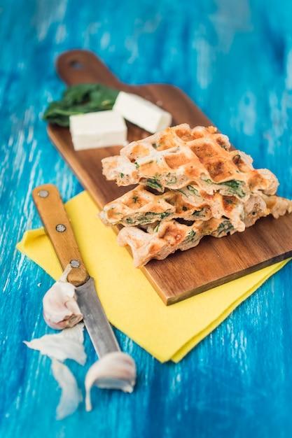 Erhöhte ansicht von salzigen waffeln auf holzbrett mit käse; messer und knoblauchzehen über blauem strukturiertem hintergrund Kostenlose Fotos
