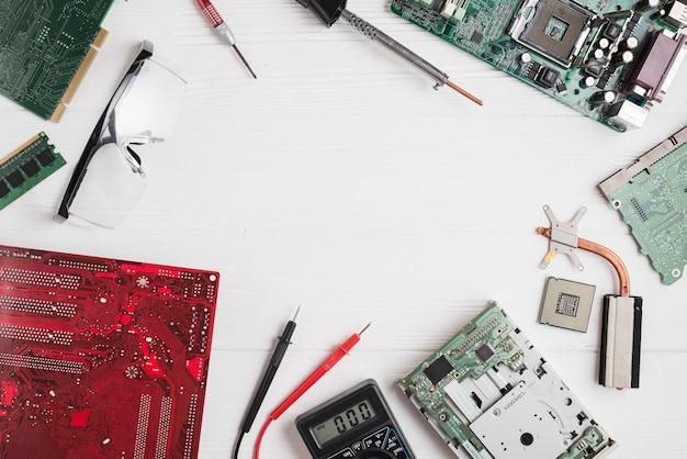 Erhöhte ansicht von verschiedenen computerteilen mit werkzeugen und sicherheitsgläsern auf hölzernem schreibtisch Kostenlose Fotos