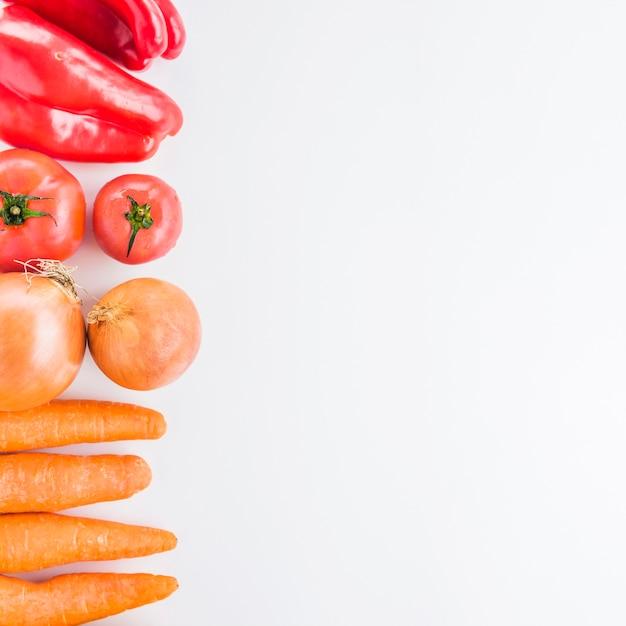 Erhöhte die karotten; zwiebeln; tomaten und roter paprika auf weißen hintergrund Kostenlose Fotos