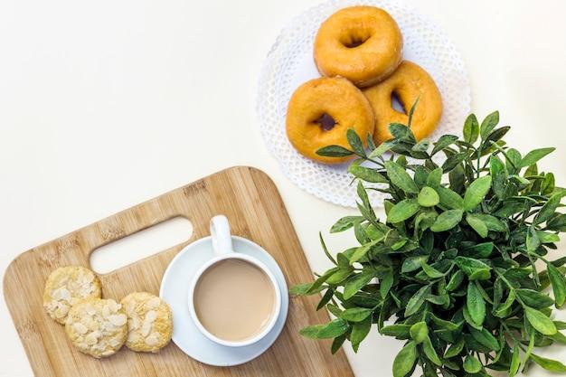 Erhöhter blick auf tee, kekse und donuts Kostenlose Fotos