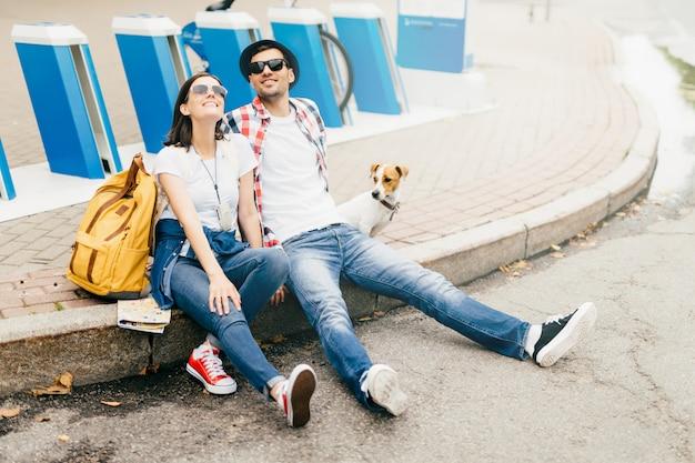 Erholsame junge männliche und weibliche reisende und ihr haustier, die auf pflasterung, nette ausdrücke beim genießen des guten wetters habend sitzen und sind nach langem weg im park erschöpft. reisendes konzept Premium Fotos
