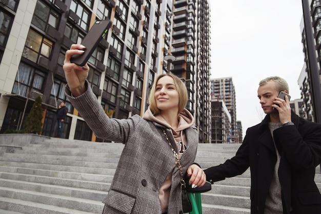 Erinnere dich an diesen moment! junge frau, die smartphone hält und selfie mit ihrem freund nimmt. junges paar, das in der herbststadt geht. wohnblöcke auf hintergrund. mann spricht am telefon. Premium Fotos