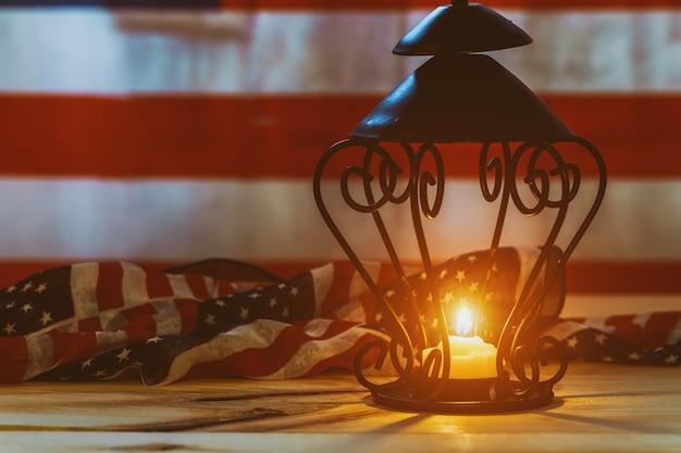 Erinnerungsschuß von einer kerzenflamme auf us-flaggenhintergrund Premium Fotos