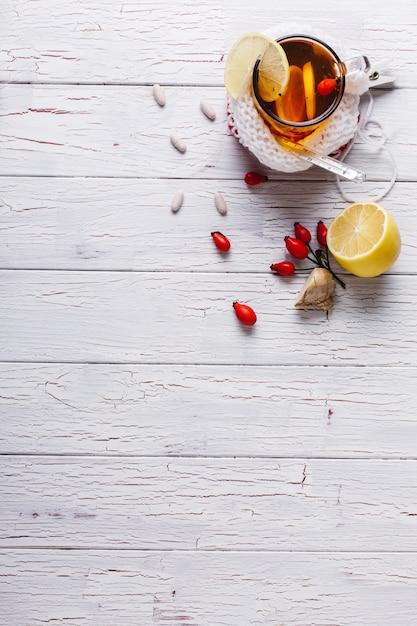 Erkältung behandeln. schale mit heißem tee mit zitrone und beeren steht auf einer tabelle Kostenlose Fotos
