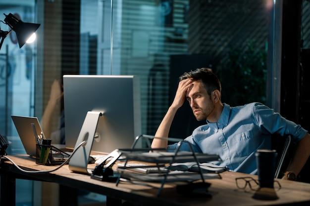 Ermüdungsmann, der computer bei der arbeit beobachtet Premium Fotos