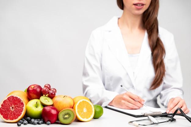 Ernährungswissenschaftler, der einen gesunden fruchtsnack isst Kostenlose Fotos