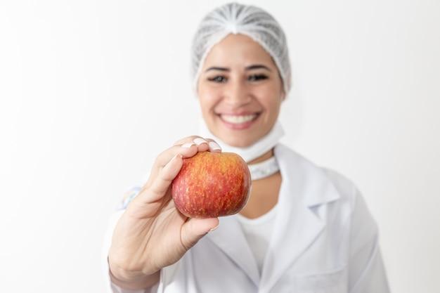 Ernährungswissenschaftler der jungen frau, der eine apfelfrucht hält. frau doktor Premium Fotos