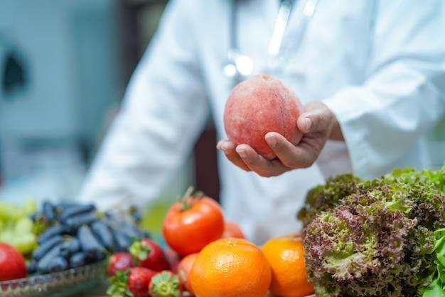 Ernährungswissenschaftlerdoktor, der in der hand früchte hält. Premium Fotos