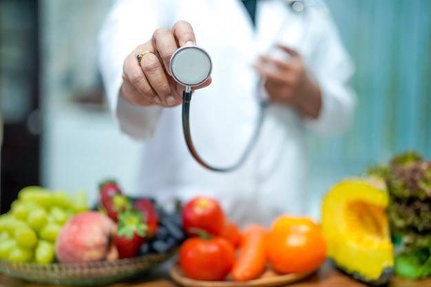 Ernährungswissenschaftlerdoktor, der orange mit verschiedenen obst und gemüse hält. Premium Fotos