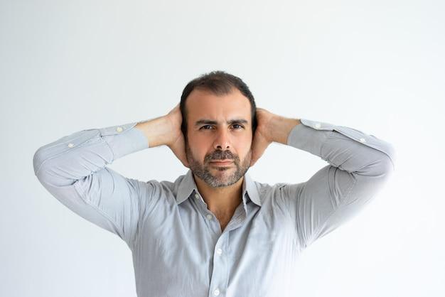 Ernste bedeckungsohren des gutaussehenden mannes mit den händen Kostenlose Fotos