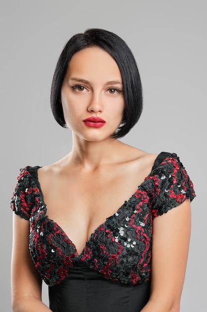 Ernste dame mit dem kurzen dunklen haar und den roten lippen, die im studio aufwerfen Premium Fotos