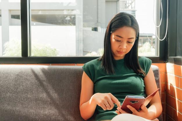 Ernste frau benutzen ihren smartphone auf dem sofa in der ecke des cafés. Premium Fotos