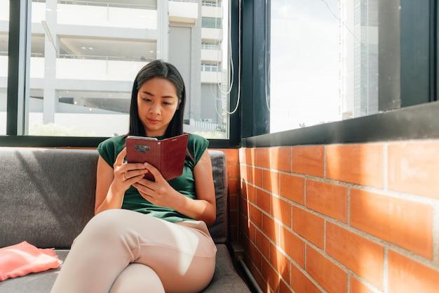 Ernste frau benutzen ihren smartphone auf dem sofa Premium Fotos