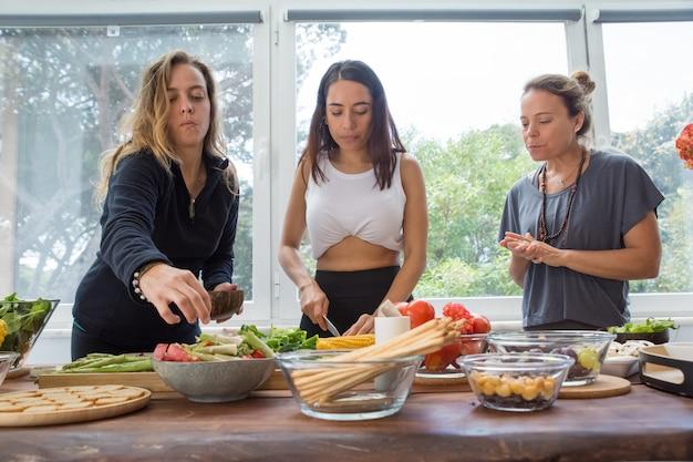 Ernste frauen, die gemüse am küchentisch kochen Kostenlose Fotos