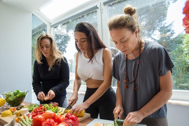 Ernste frauen, die gemüse in der küche kochen und schneiden Kostenlose Fotos