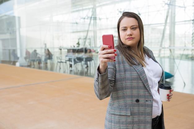 Ernste geschäftsfrau, die draußen selfie foto am telefon macht Kostenlose Fotos