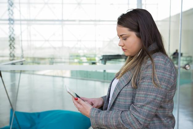 Ernste geschäftsfrau, die draußen tablette verwendet Kostenlose Fotos
