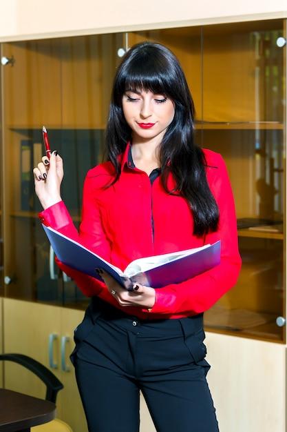 Ernste junge frau in der roten bluse mit einem ordner von dokumenten im büro Premium Fotos