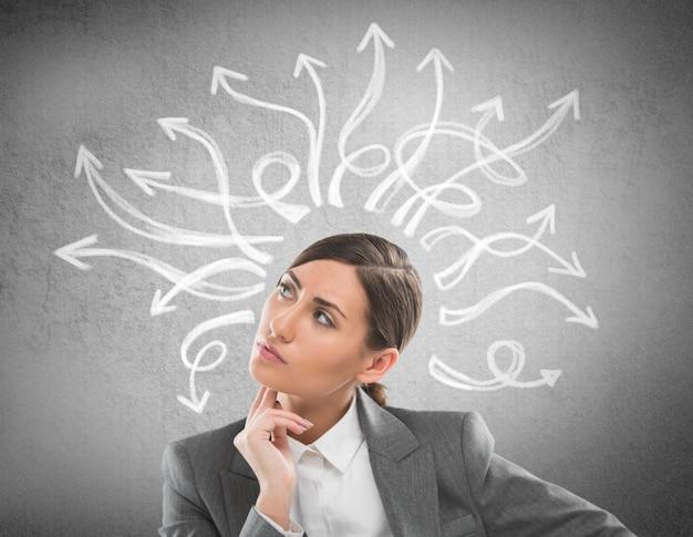 Ernste, junge geschäftsfrau, die viele verdrehten pfeile auf den betonmauerunkosten betrachtet Premium Fotos