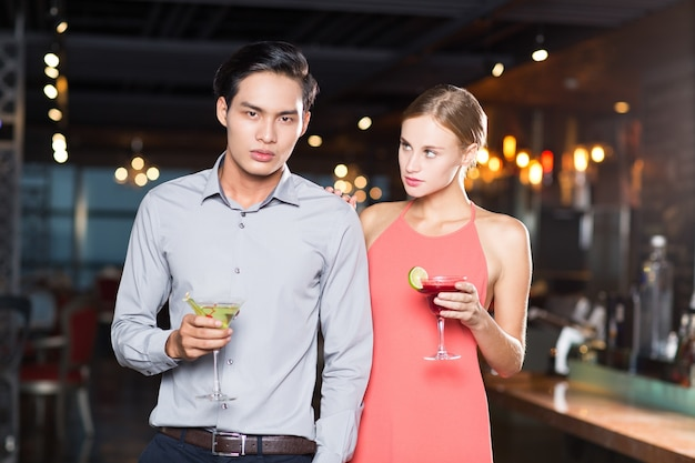 Ernste junge paare mit cocktails in bar Kostenlose Fotos