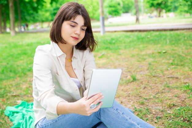 Ernste nachrichten der jungen frau leseauf tablette und sitzen auf rasen Kostenlose Fotos