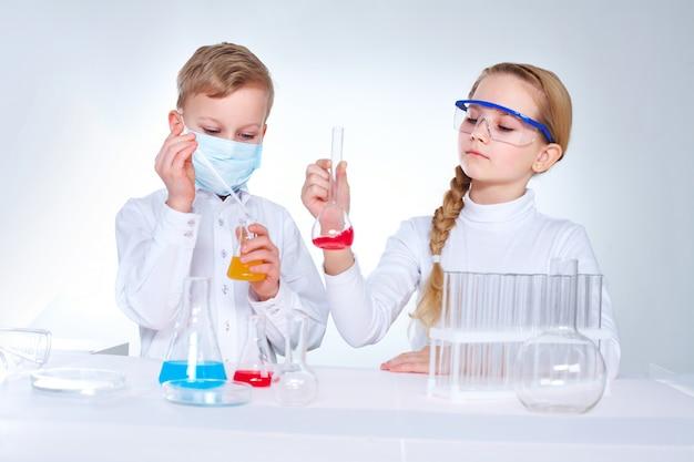 Ernste schülerin suchen kolben mit chemischer flüssigkeit Kostenlose Fotos