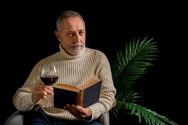 Ernster älterer mann mit buch und wein Kostenlose Fotos