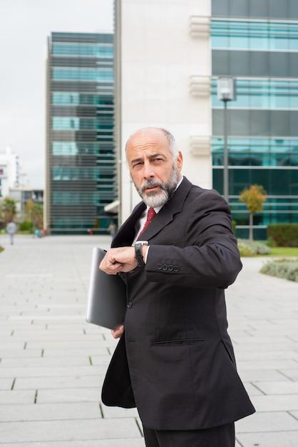 Ernster beschäftigter reifer geschäftsmannlaptop auf seinem weg zum büro Kostenlose Fotos