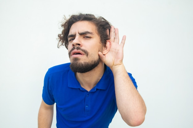 Ernster fokussierter kerl, der auf geheimnis hört Kostenlose Fotos