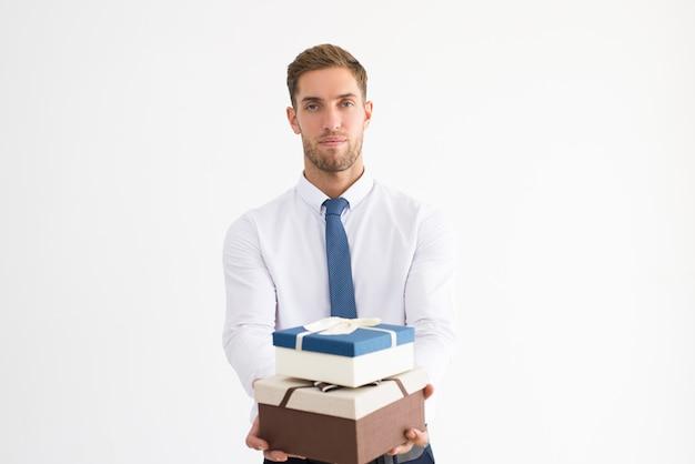 Ernster geschäftsmann, der zwei geschenkboxen mit bandbögen hält Kostenlose Fotos