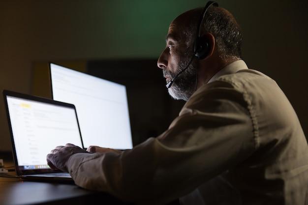 Ernster geschäftsmann im kopfhörer unter verwendung des laptops Kostenlose Fotos