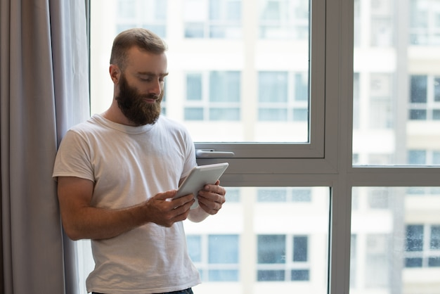 Ernster hübscher hippie-kerl, der zu hause digitale tablette verwendet Kostenlose Fotos