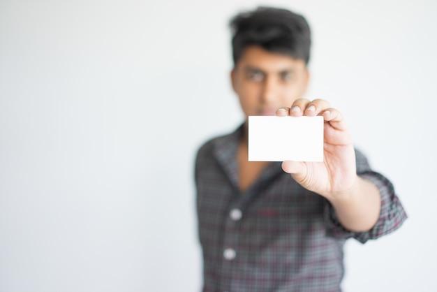 Ernster indischer mann in der freizeitkleidung, die leere karte zeigt. Kostenlose Fotos