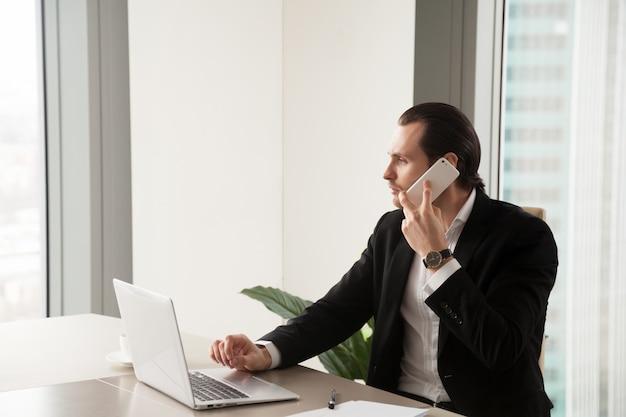 Ernster junger geschäftsmann im büro, das telefonanruf macht. Kostenlose Fotos