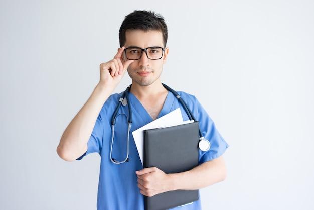 Ernster junger männlicher doktor, der ordner und dokumente hält Kostenlose Fotos