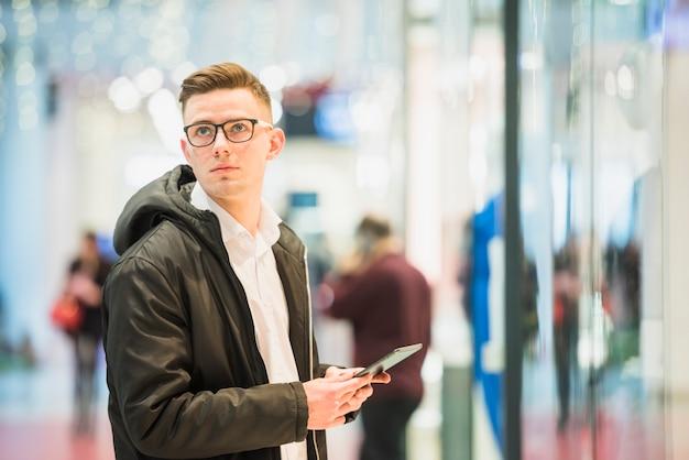 Ernster junger mann, der in der hand die digitale tablette weg schaut hält Kostenlose Fotos