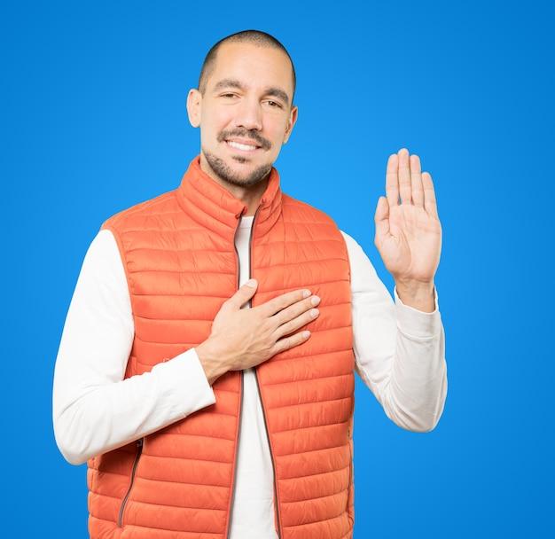 Ernster junger mann mit einer geste des eides Premium Fotos