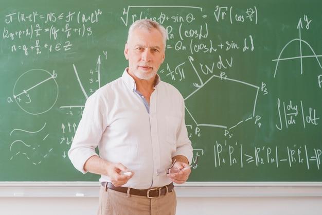 Ernster männlicher lehrer, der an der tafel mit diagramm und gleichung steht und kamera betrachtet Kostenlose Fotos