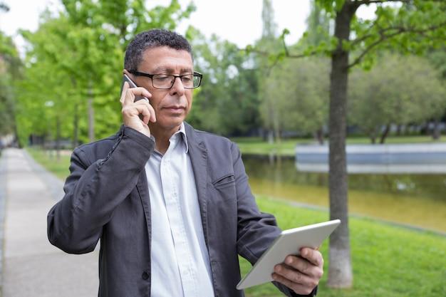 Ernster mann, der auf tablette grast und am telefon im park spricht Kostenlose Fotos