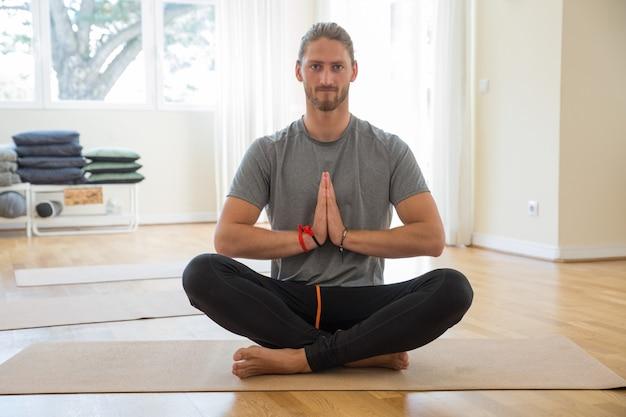 Ernster mann, der hände an der yogaklasse zusammenhält Kostenlose Fotos