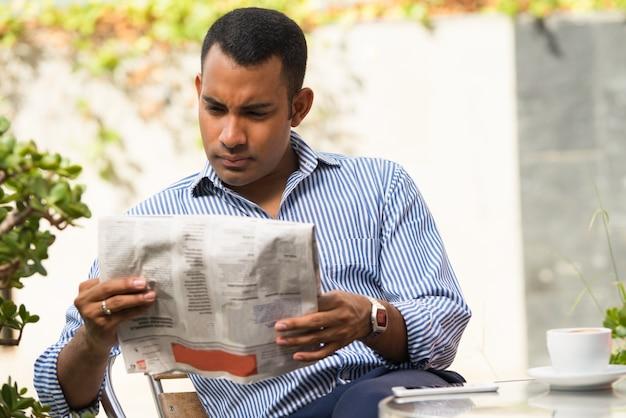 Ernster mann, der zeitung im im freiencafé liest Kostenlose Fotos