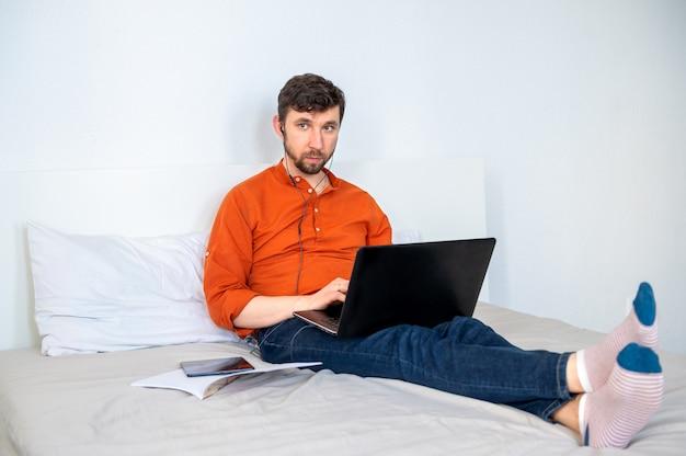 Ernster mann, der zu hause mit laptop arbeitet Premium Fotos
