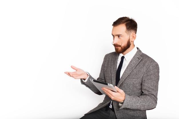 Ernster mann in der grauen klage spricht etwas, das tablette in seinem arm hält Kostenlose Fotos