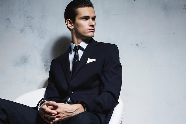 Ernster mann in einem schwarzen anzug, der auf einem weißen stuhl auf einem weißen grungy hintergrund sitzt. studio schießen Premium Fotos