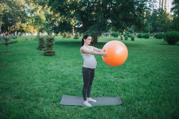 Ernster stand der jungen schwangeren frau auf yogakamerad outisde im park. sie trainieren mit großen orange fitness-ball. model halte es vor sich. Premium Fotos