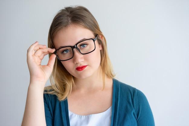 Ernstes mädchen mit den roten lippen, die brillen justieren Kostenlose Fotos