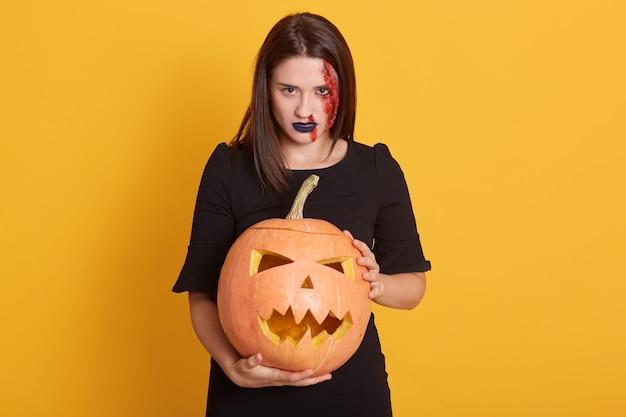 Ernstes mädchen mit wütendem gesichtsausdruck stehend mit kürbis in den händen im studio lokalisiert auf gelber, attraktiver frau mit blutiger wunde auf ihrem gesicht, halloween-konzept. Kostenlose Fotos