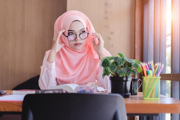 Ernsthaft asiatische moslemische geschäftsfrau haben kopfschmerzen im büro. Premium Fotos