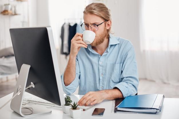 Ernsthaft konzentriert auf arbeit büroangestellte mit hellem haar, bart in lässigem outfit und brille, bereitet bericht vor, benutzt tastatur, trinkt kaffee, arbeitet während der mittagspause, sitzt gegen büroeinrichtung. Kostenlose Fotos