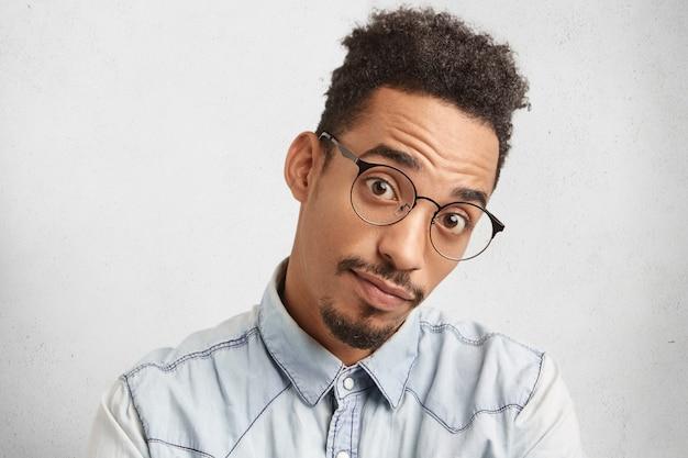 Ernsthaft überraschter mann mit ovalem gesicht, spezifischem aussehen, blick durch große brille, Kostenlose Fotos
